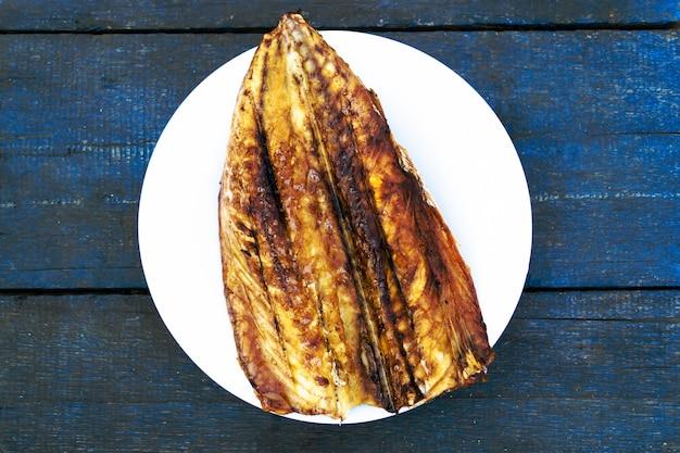 Pesce sgombro al forno su un piatto bianco