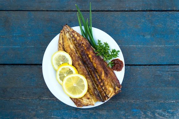 Pesce sgombro al forno con fette di limone su un piatto bianco