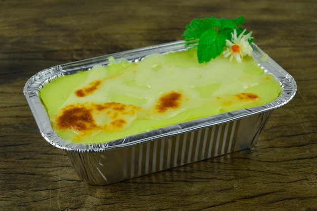 Purè di patate al forno con formaggio in vassoio di alluminio piatto fusion europeo in stile italiano decorato con foglie di menta vista laterale