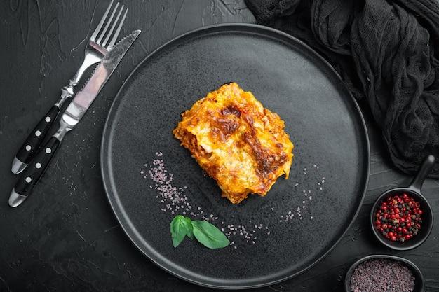 Lasagne di carne al forno sulla piastra su pietra nera