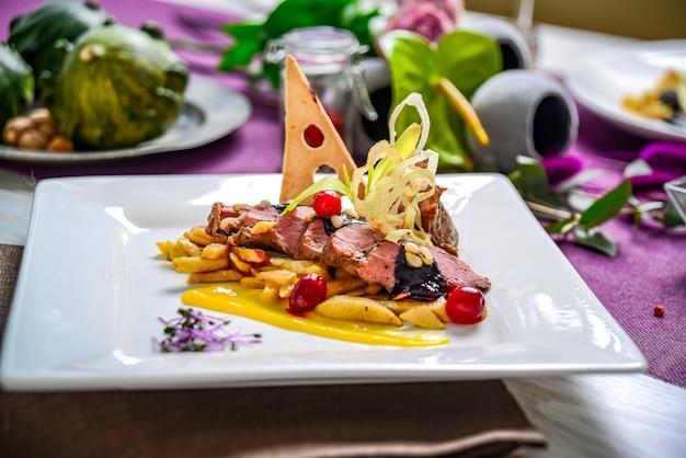 Carne al forno con patate fritte e salsa ai frutti di bosco. piatto nel ristorante