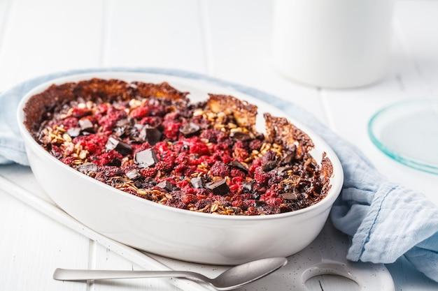 Farina d'avena al forno con frutti di bosco e cioccolato in un piatto bianco