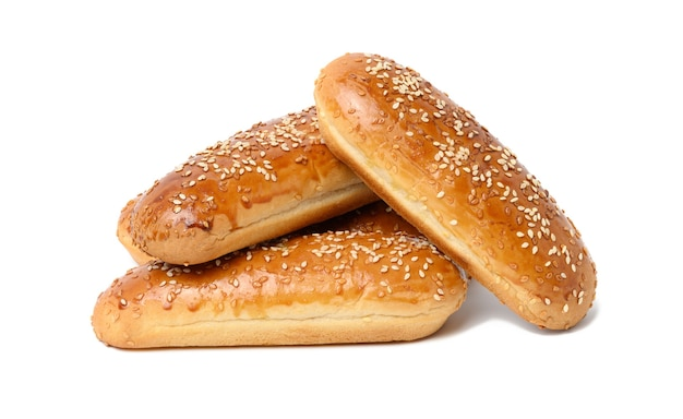 Panino per hot dog al sesamo oblungo al forno isolato su sfondo bianco, stack
