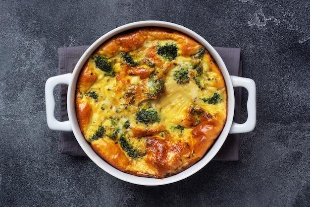 Frittata al forno con broccoli in un piatto di ceramica. tavolo in cemento scuro. copia spazio. piatto di dieta sana.