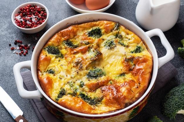 Frittata al forno con broccoli in un piatto di ceramica. tavolo in cemento scuro. piatto di dieta sana.