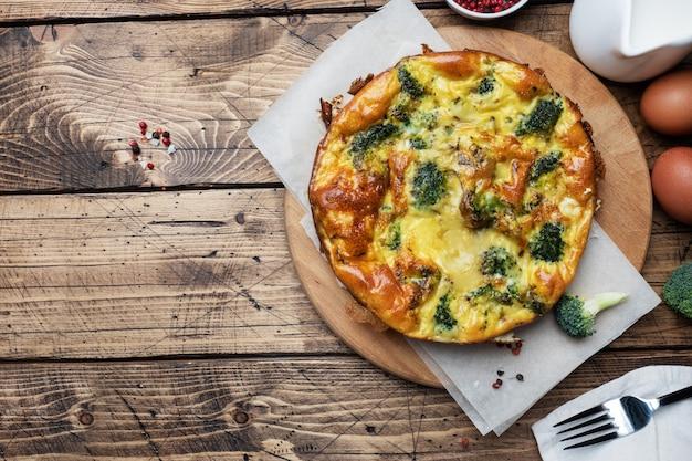 Frittata al forno con broccoli su una tavola di legno e. copia spazio. piatto di dieta sana. Foto Premium