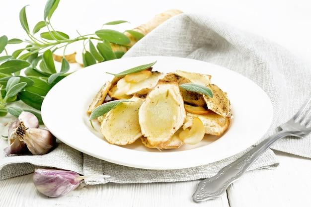 Pastinaca al forno con spezie, aglio e salvia in piatto sullo sfondo di una tavola di legno chiaro
