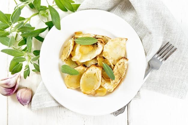 Pastinaca al forno con spezie, aglio e salvia in un piatto su un tovagliolo su tavola di legno