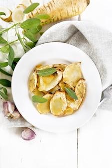 Pastinaca al forno con spezie, aglio e salvia in un piatto su un asciugamano su sfondo di tavola di legno dall'alto