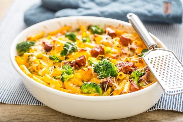 Penne di pasta al forno con mozzarella di collo di maiale affumicato ai broccoli e altri ingredienti.