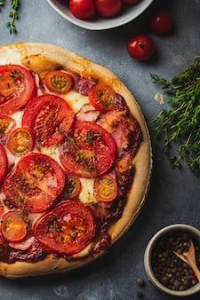 Pizza al forno con pasta integrale, pomodoro, prosciutto, mozzarella, salsa di pomodoro, timo servito su sfondo grigio pietra con vari ingredienti per cucinare.