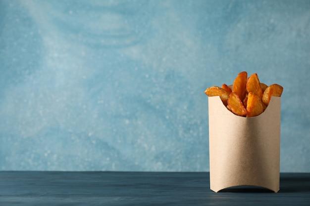 Spicchi di patate al forno in scatola sul tavolo blu sul colore