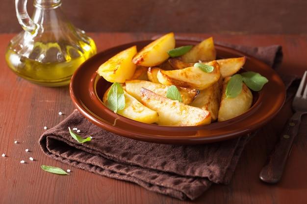 Spicchi di patate al forno in lamiera sopra tavolo rustico marrone