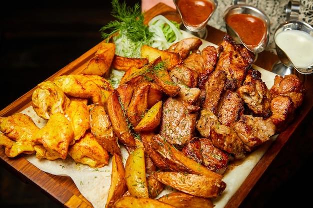 Patate al forno e verdure grigliate con spiedini e salsicce. primo piano, messa a fuoco selettiva