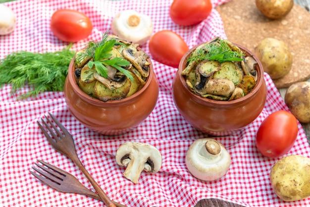 Patate al forno con pollo e funghi in una pentola di terracotta a casa.