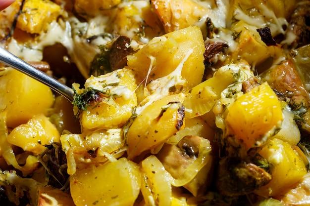 Patate al forno con funghi e formaggio con condimenti ed erbe aromatiche