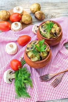 Patate al forno con funghi e condimenti vari. in vasi di argilla. vegetariano.