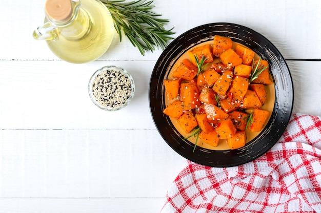 Pezzi di zucca al forno con spezie ed erbe aromatiche su fondo di legno bianco.