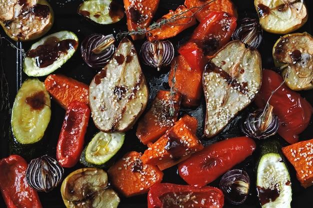 Zucca al forno, zucchine, paprika, pera, mela, cipolla blu con erbe e spezie su una teglia. mix di frutta e verdura al forno. pranzo vegano