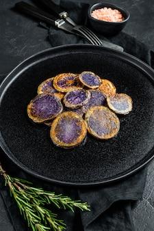 Patate viola al forno con rosmarino. sfondo nero. vista dall'alto