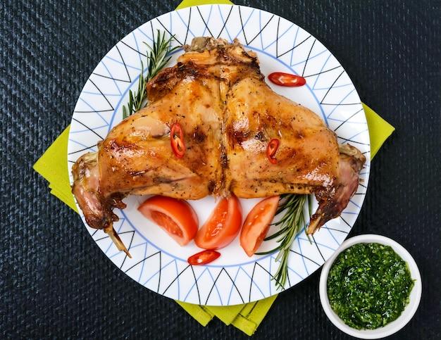 Cosce di coniglio al forno su un piatto su uno sfondo nero