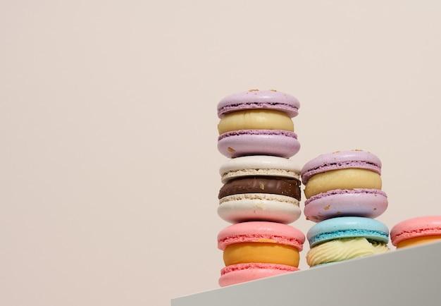 Macarons rotondi al forno su fondo beige, dessert delizioso, vista dal basso