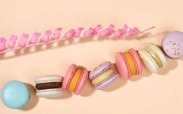 Macarons rotondi al forno su fondo beige, dessert delizioso, vista dall'alto