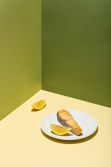 Filetto di salmone al forno con limone su piastra bianca dura moderna ombra sfondo verde foto di alta qualità