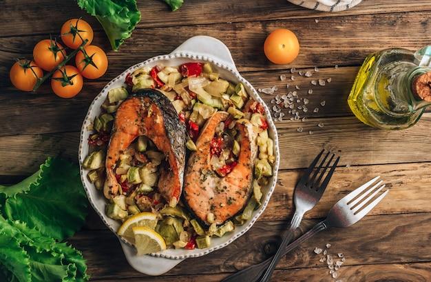 Trancio di salmone al forno con verdure su fondo rustico in legno. concetto di cibo sano. messa a fuoco selettiva