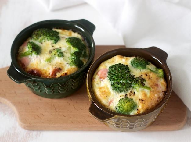 Uova strapazzate al forno con broccoli, salsicce e formaggio servito con fette di pane. stile rustico.
