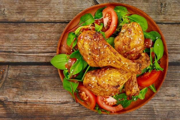 Bacchette di pollo piccanti al forno con insalata su fondo rustico in legno. vista dall'alto.