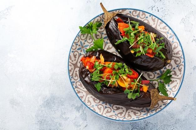 Melanzane ripiene al forno con diverse verdure, pomodoro, peperone, cipolla e prezzemolo su sfondo grigio tavolo in pietra o cemento. vista dall'alto