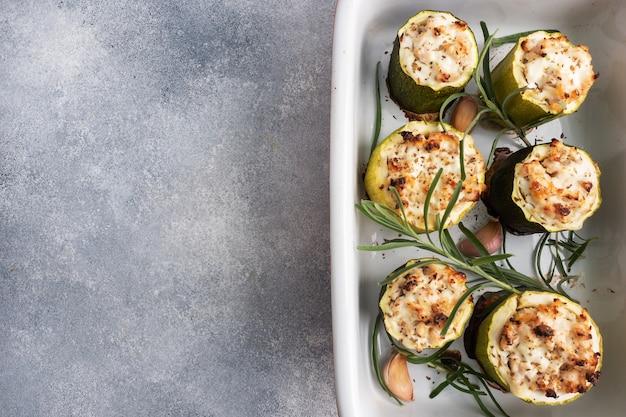 Zucchine ripiene al forno con pollo tritato e verdure in una pirofila di ceramica.