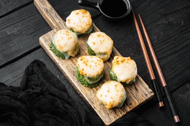 Rotoli di maki di sushi al forno con salmone, granchio, cetriolo, avocado, uova di pesce volante e salsa piccante, su tavolo di legno nero