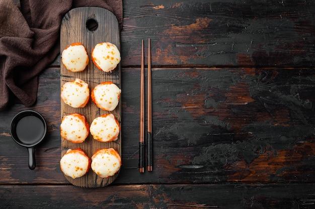 Rotoli di sushi maki al forno con salmone, granchio, cetriolo, avocado, uova di pesce volante e salsa piccante insieme, sul vecchio tavolo in legno scuro