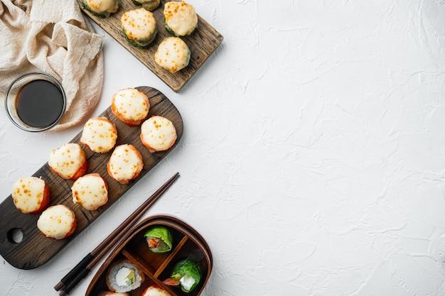 Rotoli di sushi maki al forno con salmone, granchio, cetriolo, avocado, uova di pesce volante e salsa piccante, su pietra bianca