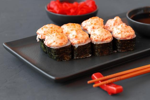 Rotolo di sushi al forno servito sulla banda nera sulla tavola di legno