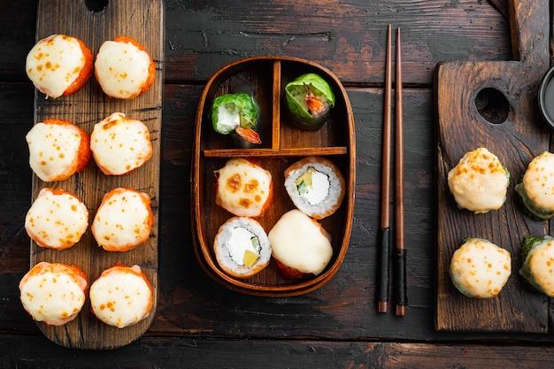 Rotolo di sushi al forno con gambero e tappo di caviale di masago. set di piatti da ristorante di sushi tradizionale, su un vecchio tavolo di legno scuro