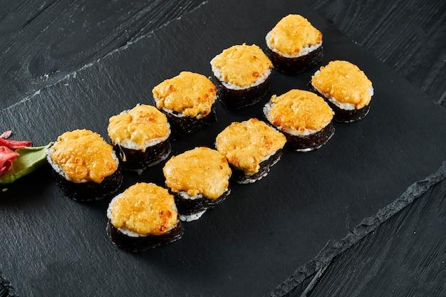 Rotoli di sushi al forno con tappo di formaggio e ingredienti diversi su una tavola di ardesia nera. cibo tradizionale giapponese