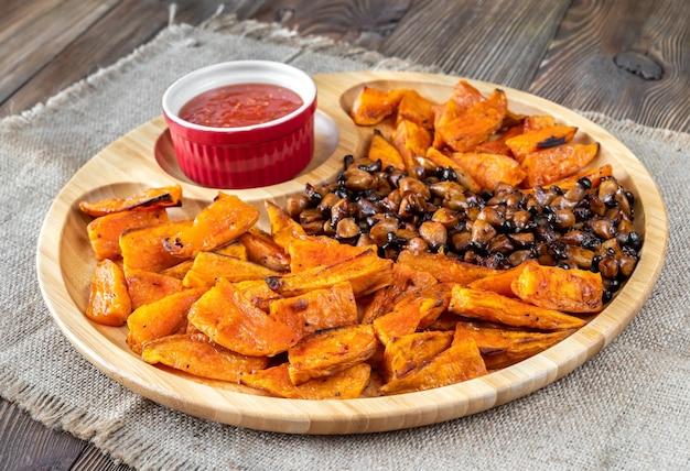 Patata dolce al forno con funghi fritti sul vassoio in legno
