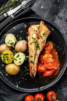 Rana pescatrice al forno con pomodori, patate e verdure