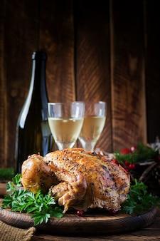 Tacchino o pollo al forno. la tavola di natale è servita con un tacchino, decorato con orpelli luminosi. pollo fritto, tavola. cena di natale.