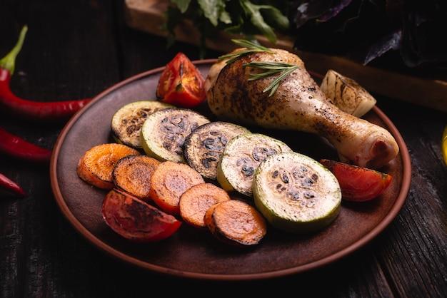 Verdure al forno su un piatto, coscia di pollo alla griglia, cena deliziosa,