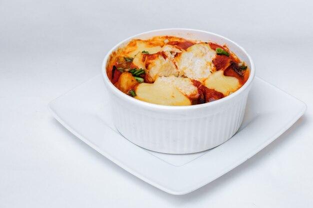 Verdure al forno zucchine e pomodori con formaggio. isolato su bianco dal percorso di residuo della potatura meccanica. avvicinamento