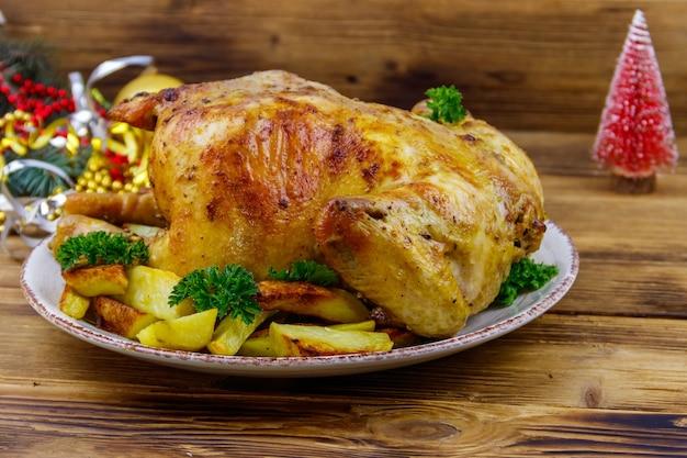Pollo intero al forno con patate e decorazioni natalizie su un tavolo di legno