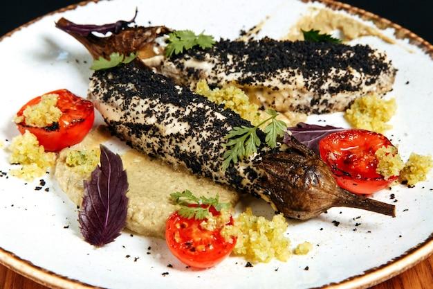 Zucchine al forno con hummus e pomodoro grigliato in un piatto bianco