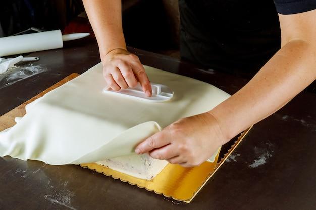 Baker che copre la torta quadrata con fondente bianco. tecnica per fare la torta.