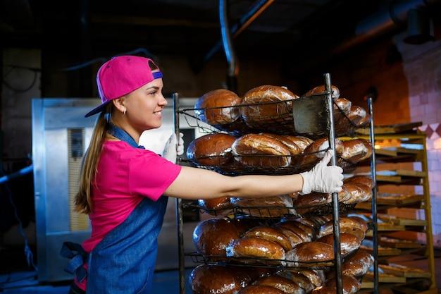 Una fornaia prende il pane caldo in una panetteria sullo sfondo di scaffali con il pane. produzione industriale di pane. la fase di cottura in una panetteria