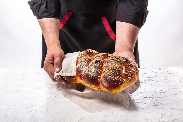 Panettiere che tiene pane ebreo challah al forno fresco
