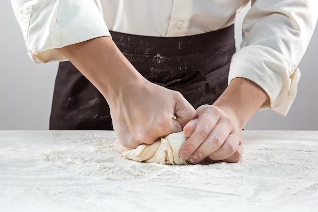 Il panettiere che fa il pane, mani maschili, impasta, cucina il cappotto